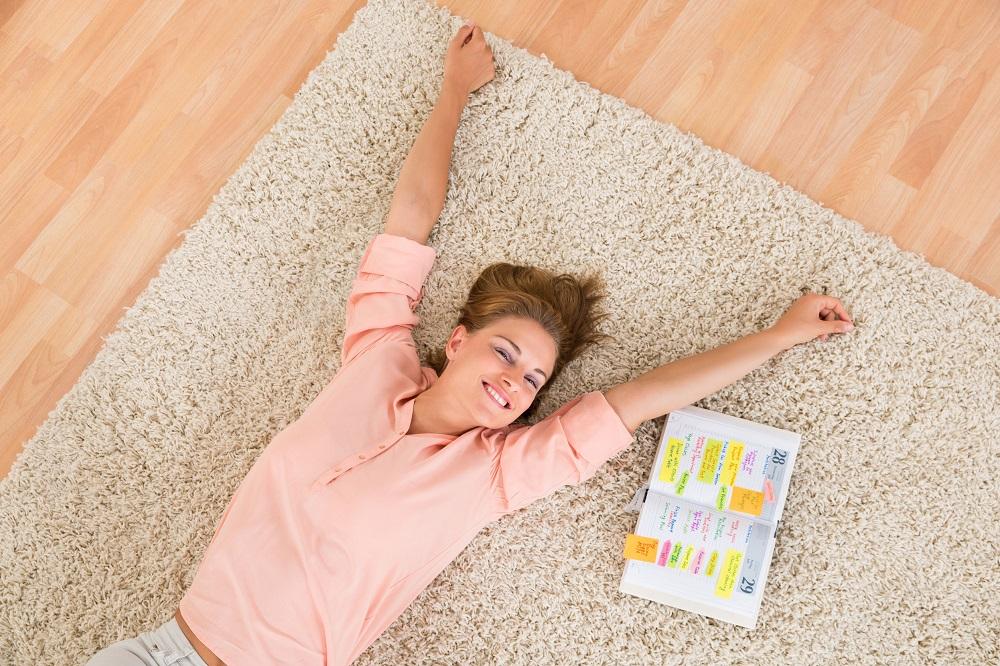 בחורה שוכבת על שטיח נקי