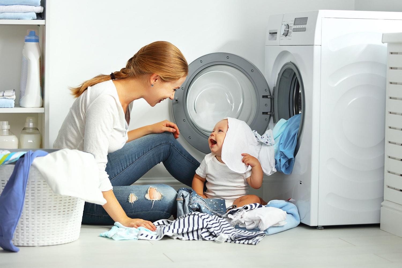 אמא עושה כביסה עם תינוק לידה